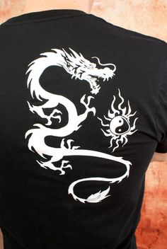 The dragon is a symbol of power, strength, wisdom, protection and good luck. The Yin and Yang also adds balance to this unique dragon symbol.  This is a very soft and comfortable mens short sleeve tee-shirt. The White dragon is screen printed on the back. Tee Comes in many colors!  Choose your own color shirt, or mix and match EXISTING symbols and slogans with existing shop shirts to create your own design at NO EXTRA CHARGE!! {Materials} 100% Cotton. Eco-friendly. This is a premium quality…