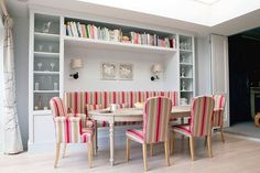 Banquette seating for the Scandinavian dining space with smart shelves all around and colorful chairs [Design: Fiona Andrews Interiors Limited] | Lacking some inspiration to decorate a dining room in style, we've got you covered | www.bocadolobo.com #bocadolobo #luxuryfurniture #luxurydesign #bespoke #furnituredesign