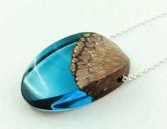 Diese atemberaubende Halskette ist eine Verschmelzung aus brilliantem Blau mit exotischem australischem Banksia Holz. Ein großartig handgeschliffenes Oval, das transluzente Harz bietet einen wunderschönen Kontrast zu dem satten und strukturierten Holz. Der Anhänger hat einen Umfang von 40x25x10mm. Eine Gliederkette nach Wahl entweder aus 925 Sterling Silber oder 750 vergoldet in vier verschiedenen Längen oder ein schwarzes Lederband (1mm). Klemmverschluss. Die Kette wird im weißen…