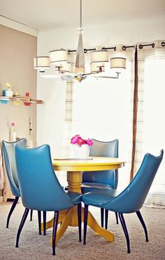 Yellow table and blue chairs. Really interesting look with the high back retro chairs.