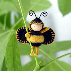 """bumblebee stands 1 1/2"""" tall ... it is made of a wire core covered in cotton floss ... it is bendable and can hold onto objects ... its torso is needle-felted merino wool, hat is wool felt stitched with tiny blanket stitches and has a wooden bead head with two black wire antenna ... no tutorial"""