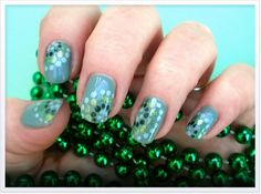 Fingernails wearing no chip long lasting Gelibility gel nail polish green spiral dots nail art next to green beads on a green background.