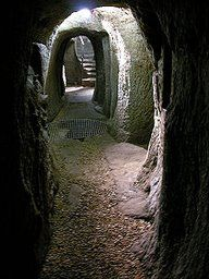 passageway in Gilmerton Cove, Edinburgh, Scotland    Gilmerton Cove is a series of underground passageways and chambers hand-carved from sandstone located beneath the streets of Gilmerton, an ex-mining village, now a suburb of Edinburgh, Scotland. There are many theories about why it was built--drinking den, smuggler's lair, refuge--but no definitive answer has been found.