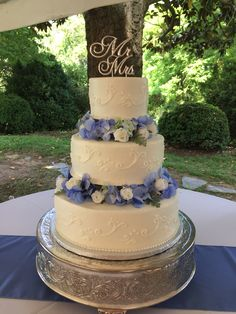 Three tier buttercream wedding cake decorated with silk flowers and simple piping.