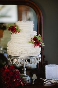 Ruffled white wedding cake with red flowers
