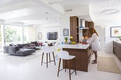 Maury Strong makes coffee in the kitchen of the 2,400-square-foot bungalow she renovated <br>with her husband, Ron Caron.The overall light palette includes white Caesarstone countertops <br>and limestone floors. The Bacco stools were purchased through Design Within Reach's eBay outlet.