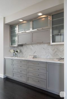 Soft patterning is added in the kitchen's buffet area with a Herringbone Calacatta tile backsplash. The gray painted cabinets have a more modern feel with frosted glass fronts andbrushed stainless hardware.