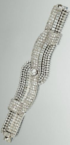 DIAMOND BRACELET, CIRCA 1935 The articulated band designed as stylised loose ribbons, set to the centre with a circular-cut diamond in a collet-setting, within surrounds of pavé-set and collet-set circular- and single-cut stones and channel-set baguette and step-cut diamonds, mounted in platinum,  French assay marks. length approximately 185mm,