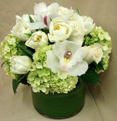 This is a floral arrangement that features roses, tulips, hydrangea and cymbidium orchids in a white and green color scheme.  See our entire selection at www.starflor.com.  To purchase any of our floral selections, as gifts or décor, please call us at 800.520.8999 or visit our e-commerce portal at www.Starbrightnyc.com. This composition of flowers is generally available for same day delivery in New York City (NYC).  LV013