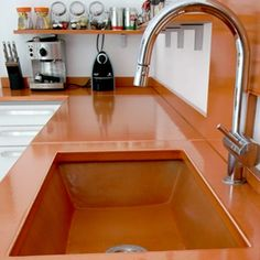 Terracotta colored lava stone countertop paired with a similar colored sink, modern stainless faucet.