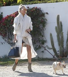 Chrissy Teigen took her adorable dog out for a walk dressed in a floaty white coat and oversize scarf.