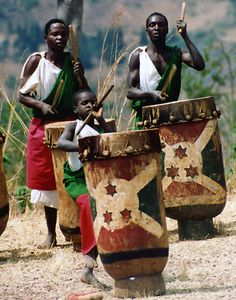 """A small boy in Burundi joins more experience drummers in an impromptu performance of """"Les Tamborines""""."""