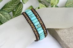 This Turquoise beaded leather cuff features 3 rows of genuine leather, quality gemstone and glass beads. So easy to wear, simply wrap once around your wrist and fasten the button for a stylish stacked look. Cuff Measurements; 1 1/4 wide. Fits up to a 6 1/2 wrist. Cuff Details; Semi Precious Gemstone Beads - Stabilized Turquoise Barrels Glass Czech Beads - Picasso finished Topaz Leather Color - Distressed Antique Brown Button - Antique Brass Sheriff Star Metal Button 18mm Thread - 10...