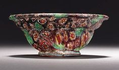 A ROMAN MOSAIC GLASS PATELLA CUP   circa late 1st century b.c.- early 1st century a.d.   Assembled from cane sections of turquoise and yellow, red and yellow, and red and white, on a purple ground, the cast carinated bowl with rounded horizontal rim, the out-splayed applied base ring with a rounded edge  3 in. (9.4 cm) in diameter; 1 in. (4 cm) high