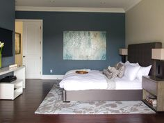 The master bedroom is designed to be soothing and modern. Colors in deep blue, white and gray