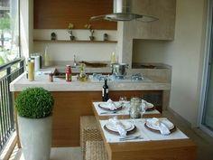 Varanda gourmet com churrasqueira. E mesa no centro.
