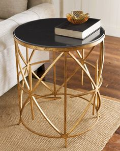 "Handcrafted side table marries a black granite top with a hand-painted antique-gold iron base. 20""Dia. x 24""T."