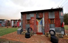 The shebeen, titled 'Shebeen' at Shanty Town on November 15 in Bloemfontein, South Africa. Shanty Town is a holiday spot where tourists can pay a night to sleep in a recreational shack. Get premium, high resolution news photos at Getty Images South African Holidays, The Shanty, Orange Uk, Derelict Buildings, Metal Siding, Lean To, Affordable Housing, Hotel Spa, Boutique