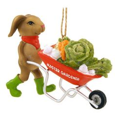 """Do you know some-<i>bunny</i> that's really into gardening? This <i>hare</i>-raising design is artfully crafted of resin with metal accents and depicts an adorable rabbit pushing a <i>garden variety</i> of veggies in a wheel barrow marked <i>Master Gardener</i>. Coming ready to hang with a silver cord, our Rabbit Gardener With Wheelbarrow Ornament measures approximately 3"""" tall x 4"""" long."""