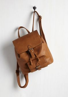 With time to spare between classes, you take a quick spin through the campus park to show off this cognac brown backpack! This vegan faux-leather bag flaunts adjustable straps, a pull-tie closure under its glistening, golden buckles, and plenty of pockets in which to store the day's worth of snacks.