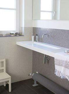 love the narrow sink & half wall of tile