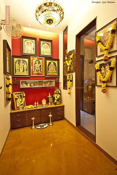 bright coloured puja room with lots of idols and wooden cabinets
