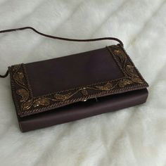 Sweet little brown clutch This is a very pretty brown fabric bag sa Coppertone beating going around it it has a small cloth strap use it as a shoulder bag or tuck it in for a clutch it is 8.5 x5 inches  Have a small mark on the top barely noticeable picture is showing it Bags
