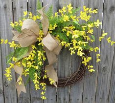 Beautiful spring wreath with a wild burlap bow, realistic forsythia, and bright green fern.