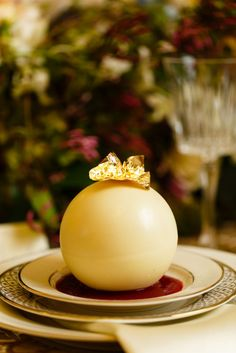 Pearlescent white chocolate globes filled with raspberry mousse atop a light vanilla sponge cake. Served with raspberry purée and topped with gold leaf flakes. From LUX Catering & Events