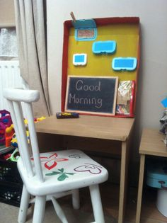 Wall protector for breakfast table. The flaps ( old baby wipe lids) hold pictures of topics that are current for us, eg a plane ride to go on holiday. The chalk board has different greeting etc on it so 'little miss' can recognise words and letters.
