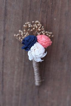 Navy blue and coral boutonniere with tan babies breath wrapped in twine.