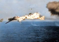 """A Japanese Nakajima B6N 'Tenzan' torpedeo bomber is hit by a 5 inch shell while attacking the USS 'Yorktown' aircraft carrier off Kwajalein Atoll, Marshall Islands, North Pacific. Mid-day on the 4th December 1943. Deck side account, """"At 300 yards, the Jap plane took a shell in its left wing and flames spurted out. The pilot then veered to try to crash into the Yorktown, skimming the flight deck so close that the flames singed the beard of one of the Yorktown gunners. The plane finally…"""