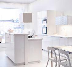 Vue d'ensemble de la cuisine IKEA, en blanc brillant. Armoires, coin repas, appareils et luminaires.
