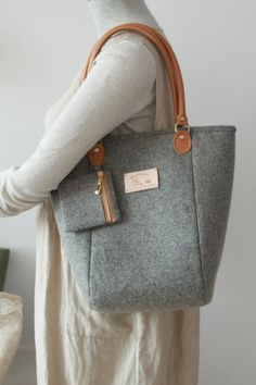 This handmade shoulder handbag is made from grey wool felt fabric with leather handle and metal feet on the bottom. Including a coin purse. Inside