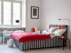 Une tête de lit recouverte d'une housse en tissu coloré et graphique