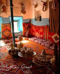 """Brass trays, brightly colored throw rugs and hangings and cushions around the perimeter of the """"hospitality"""" area."""