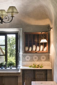 Marble countertop with marble and tile backsplash. Rustic plate rack. Italy - Tuscany