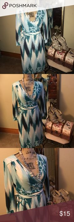 This is a beautiful wrap like dress. This dress is absolutely stunning. It's has white, light blue, navy, and turquoise. It's brand new with tags. Old Navy Dresses Midi