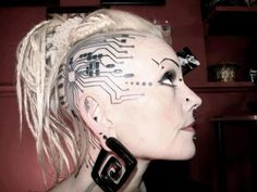 Sexy circuitry tattoo,numerous piercings, and squared spiral gauge earrings.
