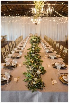 Wedding reception table at Summerour Studio in Atlanta with gray linens, gold place settings, floral chandeliers and a centerpiece garland of olive branches and white florals. Event design by Molly McKinley, florals by Victory Blooms. Image by Rustic White Photography.