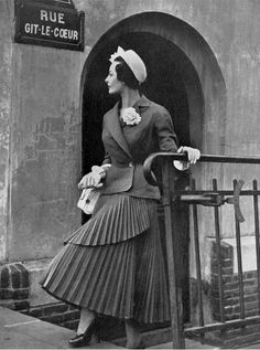 1949 Model in gray suit, skirt is pleated and wraps around like a cornet, jacket buttons on the side adorned with a rose in the lapel, by Jean Dessès