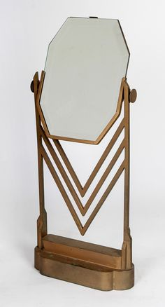American Art Deco Table Top Jewelry Salon Mirror Circa 1928. Jock Peters (1889-1934) Designer; Eleanor Lemaire (Designer) Feil & Paradise Company. Bullocks Wilshire (Los Angeles, CA) Gold toned cast bronze w/ a stepped lozenge shaped base and an upright design w/ chevron motif and side screw adjustments w/ the original octagon shaped beveled mirror. (hva)