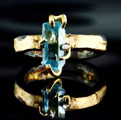 Raw Aquamarine Engagement Ring Wrapped with 18K Gold Claws a Raw Aquamarine Crystal
