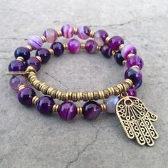 27 bead mala bracelet, made with genuine purple agate, hand made brass African Trade Beads (for sizing) and a hamsa hand charm. It wraps as a bracelet, (stringed on thick hi-tec elastic). Great on men