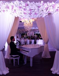 gorgeous flowers and #chandelier overhanging a simple white piano // as seen on modernwedding.com.au