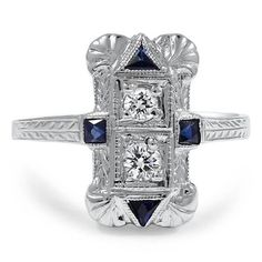 THE PETRINA RING $1,975 This rectangular shaped Art Deco ring features two round brilliant diamonds vertically set and four French cut lab created sapphires at compass points. Etched detailing on the corners and band finish this beautiful antique piece (approx. 0.17 total carat weight).