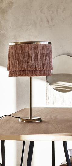 Add tasteful tassels to your living space with the Nappa Fringed Table Lamp (bulb not included).