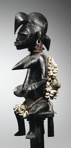 """Canne, Sénufo - Récompense décernée aux champions des cultures de chaque nouvelle génération d'initiés du Poro, la canne cérémonielle tefalipitya (ou daleu) est classiquement dominée par la représentation """"d'une jeune femme non mariée, au sommet de sa beauté : elle porte des ornements raffinés, sa tenue droite et élancée exprime sa fierté"""""""