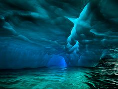 """Pleneau Bay Glacier, Antarctica Light playing off a glacier creates otherworldly hues in Pleneau Bay in Antarctica's Lemaire Channel. Photographer Eric Meola got this shot as he was in a Zodiac off the cruise ship Ocean Nova in December 2011. """"As we floated up to an enormous iceberg, we went a bit too close and made gentle contact,"""" he says, """"just long enough for me to peer at the underside, which was being carved out and sculpted by the sea and waves."""" Travel 365 -- Most Popular Photos of…"""