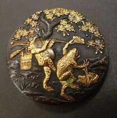 Bronze button with two toads. One has a wooden bucket hanging from a cattail, and the other dances with a fan and a petal basket